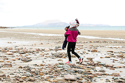 Young Girl Carries Grumpy Toddler Brother Across Rocky Irish Beach - p1166m2094753 by Cavan Images