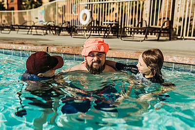 Funny image of dad in child's hat playing in the pool with sons - p1166m2218263 by Cavan Images