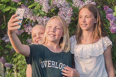three young girls taking a photo - p1323m2015180 von Sarah Toure