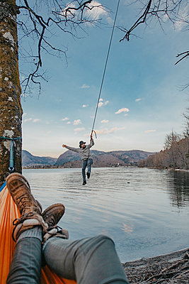 Young man on a swing next to Bohinj Lake in Slovenia - p1455m2077126 by Ingmar Wein