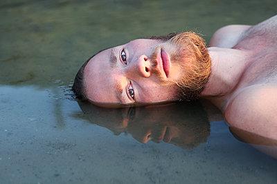 Junger mann im Wasser liegend - p1519m2124746 von Soany Guigand