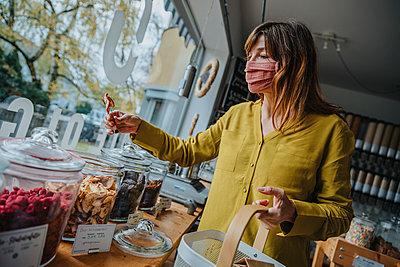 Customer picking food in zero waste shop, Cologne, NRW, Germany - p300m2256254 von Mareen Fischinger