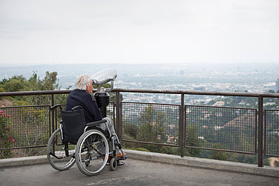 Senior man in wheelchair looking at city through coin operated binoculars from viewing balcony, Observatory, Griffith Park, Los Angeles, California, USA - p429m974680 by JLPH