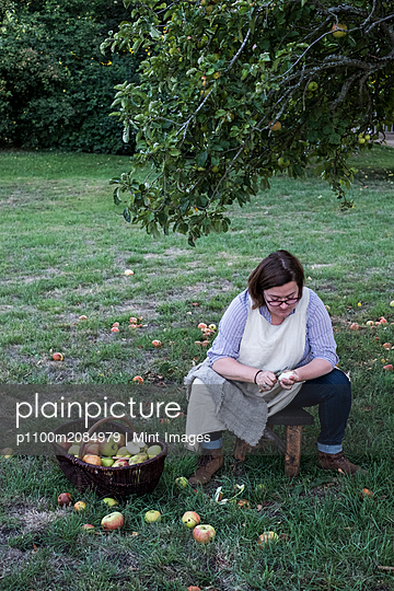 Woman sitting in an orchard under apple tree next to brown wicker basket with freshly picked apples, peeling an apple. - p1100m2084979 by Mint Images