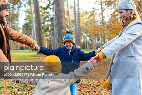 Happy family enjoying while playing in forest - p300m2256817 by William Perugini