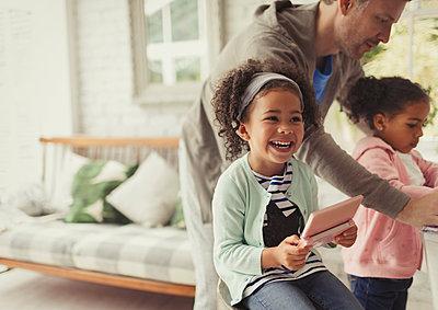 Laughing girl using digital tablet in living room - p1023m1448794 by Paul Bradbury