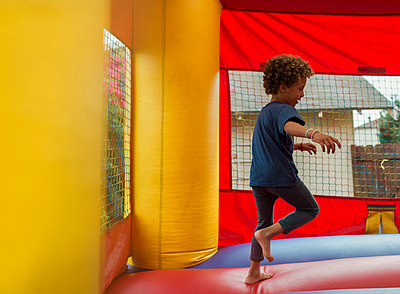 Side view of happy boy jumping on bouncy castle at park - p1166m2034461 by Cavan Images