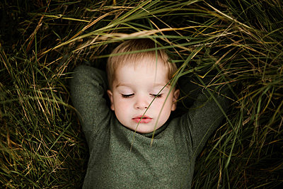 Little cute boy is lying on the green grass on a sunny day - p1166m2095445 by Cavan Images