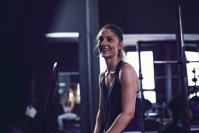 Young woman sitting and laughing after exercise at fitness centre - p1166m2095493 by Cavan Images