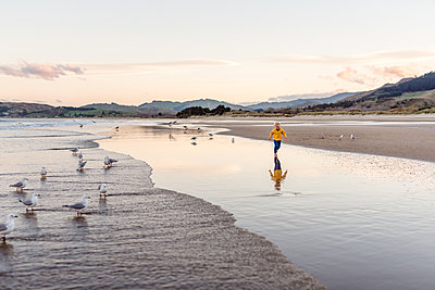 Little boy running at beach with reflection - p1166m2147541 by Cavan Images