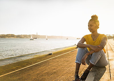 Young woman sitting at the waterfront enjoying the view at sunset, Lisbon, Portugal - p300m2160386 by Uwe Umstätter