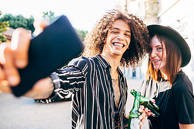 Cheerful man taking selfie with girlfriend while standing in city - p300m2206878 by Eugenio Marongiu