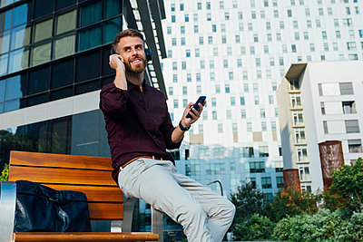 Mid adult businessman listening through headphones while sitting on bench in city - p300m2250367 by Boy photography