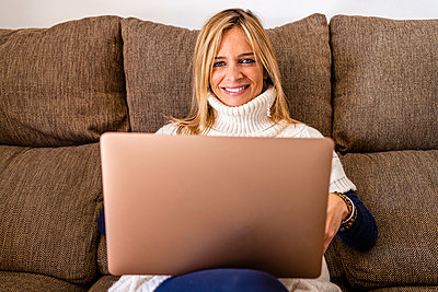 Smiling female therapist sitting with laptop on sofa at work place - p300m2250803 by Javier De La Torre Sebastian