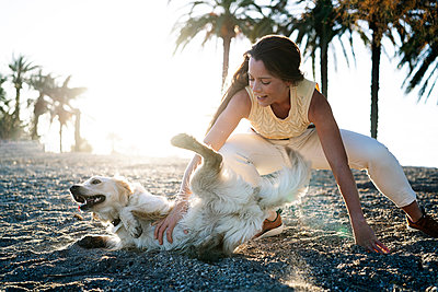 Woman with dog having fun in sand during sunny day at weekend - p300m2267004 by Manu Padilla Photo