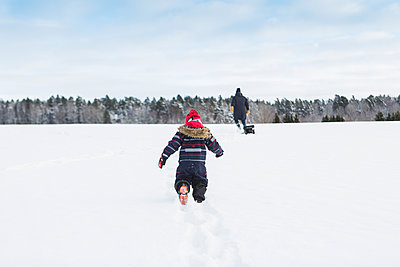 Rear view of child playing in snow - p352m1536596 by Calle Artmark