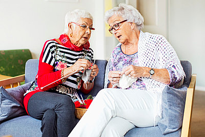 Senior women discussing while knitting at nursing home - p426m977468f by Maskot