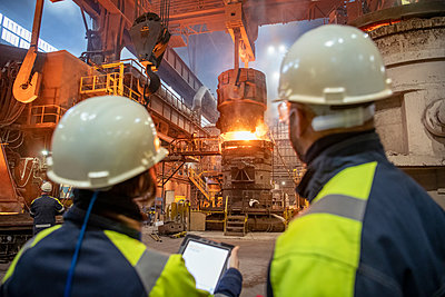 Male and female steelworkers using digital tablet during steel pour in steelworks - p429m2135022 by Monty Rakusen