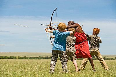 Safari guide, Salaash Ole Morompi, teaches children archery Maasai style - p6521202 by John Warburton-Lee