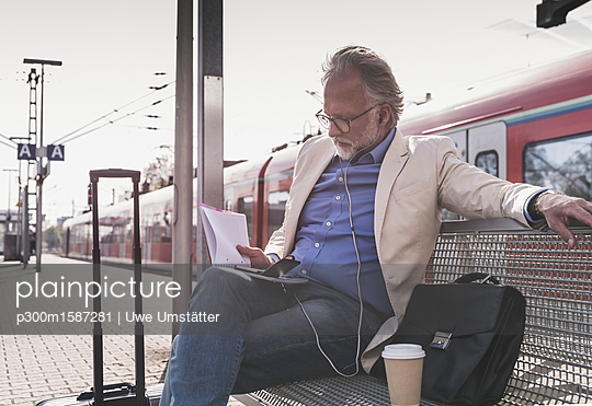 Mature businessman sitting at train station with cell phone, earbuds and notebook - p300m1587281 von Uwe Umstätter
