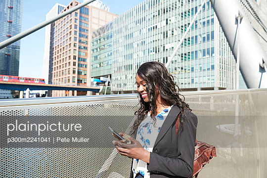 Smiling businesswoman on bridge using mobile phone on sunny day - p300m2241041 by Pete Muller
