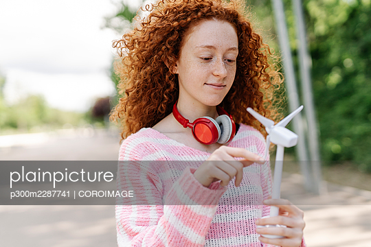 Redhead woman holding wind turbine while standing at park - p300m2287741 by COROIMAGE