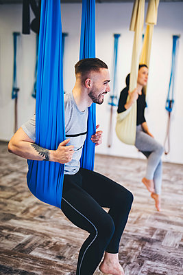 Friends sitting on hammocks while exercising in gym - p1166m1576468 by Cavan Images