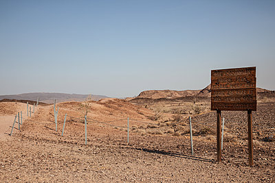 Weathered wooden sign in the desert - p1291m2172080 by Marcus Bastel