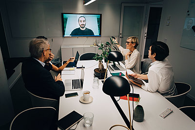 Male and female colleagues discussing with businessman through video call in board room during meeting late at night - p426m2194787 by Maskot