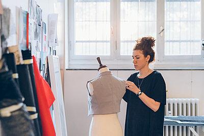 Fashion designer pinning garment onto dressmaker's dummy - p429m2058355 by Eugenio Marongiu