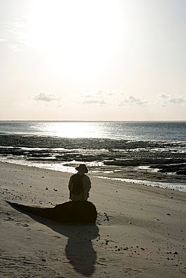 Person sitting alone at beach, Amazon, South America - p6751392 by Sandro Di Carlo Darsa