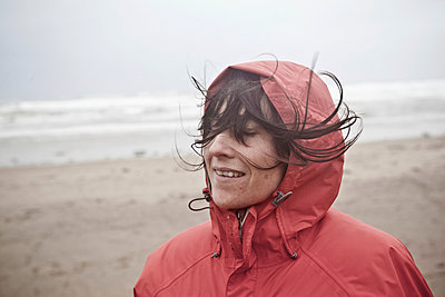 Female standing on beach in the wind wearing a red rain jacket - p686m971753 by Paul Tait