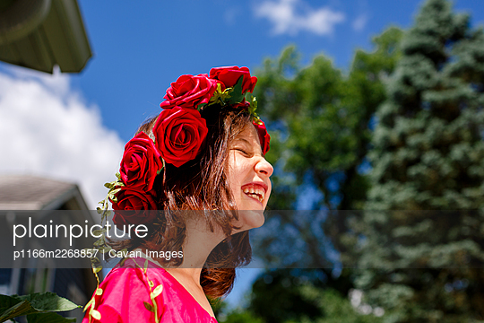 A laughing little girl with closed eyes wears a crown of roses - p1166m2268857 by Cavan Images