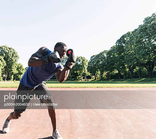Young Afro-American man training boxing on sports field, outdoors - p300m2004632 von Uwe Umstätter