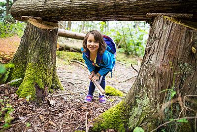 Little girl ducking under fallen tree, Chilliwack, British Columbia, Canada - p1166m2201971 by Christopher Kimmel / Alpine Edge Photography