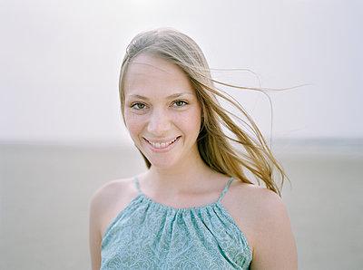 Junge Frau lächelt, Porträt - p1207m1109489 von Michael Heissner