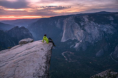 Man sitting on the edge of a big cliff with Yosemite Valley in background. Taft Point, Yosemite, CA, USA. - p1424m1500624 by Paolo Sartori