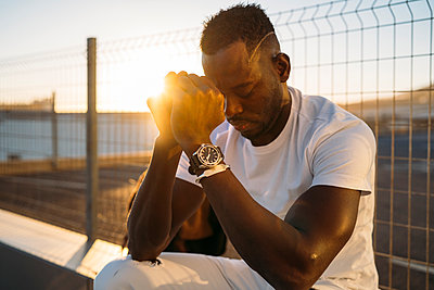 Worried African man sitting against fence during sunset - p300m2256968 by Manu Padilla Photo
