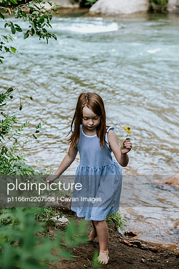 Young girl picking a flower near a river - p1166m2207958 by Cavan Images