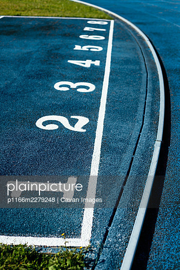 Close-up of white numbers on blue running track - p1166m2279248 by Cavan Images