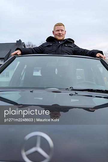 Mann blickt aus dem Schiebedach eines Autos, Portrait - p1271m2248603 von Maurice Kohl