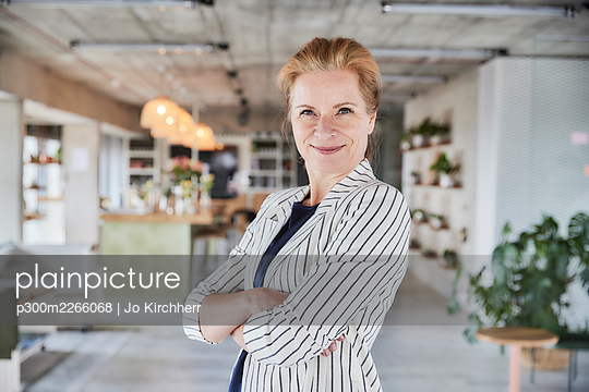Smiling businesswoman with arms crossed standing at apartment - p300m2266068 by Jo Kirchherr