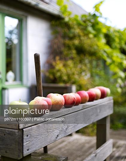 Äpfel in einer Reihe auf Holzbrüstung - p972m1160307 von Patric Johansson