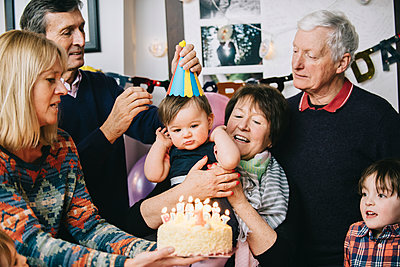 A family gathered to celebrate a one year old girl's birthday party. A cake with lots of candles. - p1100m1158513 by Mint Images