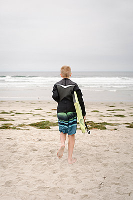 Rear view of a boy carrying a bodyboard, walking into the ocean. - p1100m1177733 by Mint Images