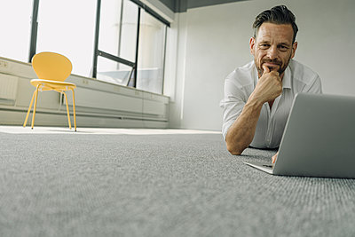 Portrait of mature businessman lying on the floor in empty office using laptop - p300m2155464 by Kniel Synnatzschke