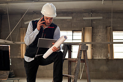 Male engineer talking over mobile phone while using digital tablet in building - p300m2244188 by Veam