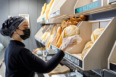 Female baker wearing mask working in bakery - p300m2281911 by Ignacio Ferrándiz Roig