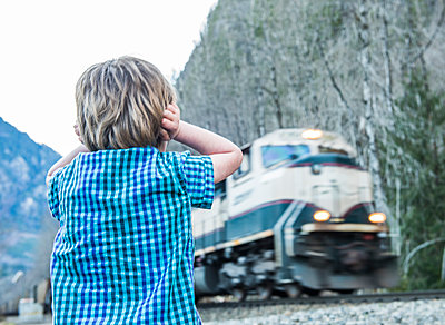 A young boy watches a train speed by at Index, Washington. - p343m1032324f by Alasdair Turner