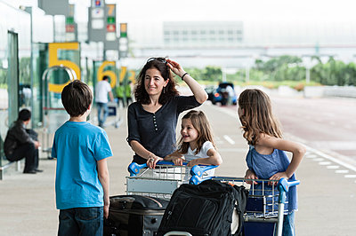 Family standing outside of airport with luggage - p623m1487510 by Thierry Foulon